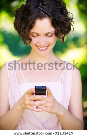 outside portrait of beautiful young curly woman reading sms in mobile phone in park - stock photo