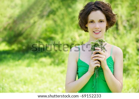 outside portrait of beautiful young curly woman with bunch of flowers in her hands - stock photo