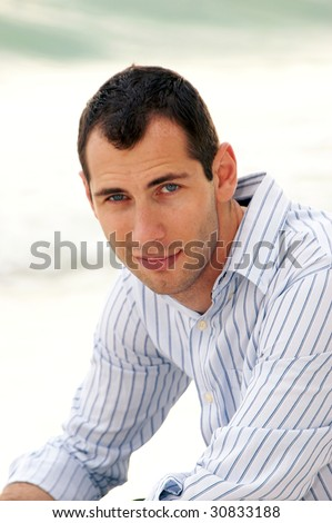 Outside portrait of clean cut young man with slight beard growth looking at viewer. - stock photo