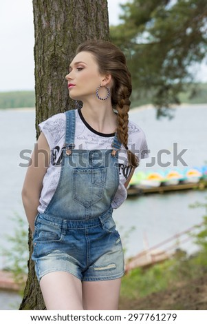 outside portrait of stylish cute woman with braid hair-style, denim overalls and trendy t-shirt posing near tree with relaxed expression and lake water on background.  - stock photo