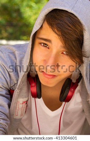 Outside portrait of teen boy. Handsome teenager  smiling and sitting on the stairs alone - stock photo