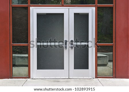Outside solid glass door with building exterior is red. - stock photo