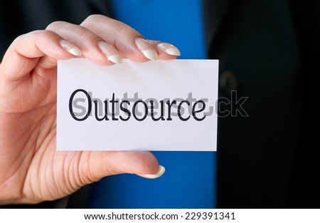 Outsource - female hand with business card - stock photo