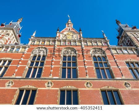 Outstanding beautiful architecture of Amsterdam train station building under blue sky, Netherlands