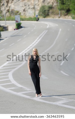 Outstanding model with a slim body do a fashion shooting on the high speed road wearing a black neck jumpsuit