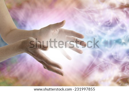 Outstretched female healing hands with white light between and vibrant energy field in background  - stock photo