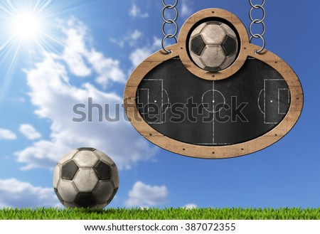 Oval blackboard with a football field (Usa Soccer) and an old ball. Hanging from a metal chain on a blue sky with clouds and sun rays - stock photo