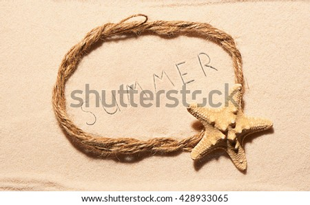 Oval frame of rope with starfish and drawn summer lettering on sand. Summer beach background. View from above - stock photo