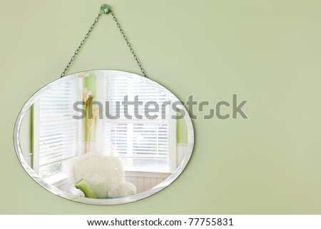 Oval mirror hanging on the wall in a summery beach house sitting area