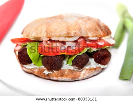 Oval vegan sandwich made from integral bred with soya barbecue cevapcici, soya cheese, onion, tomato and  lettuce serve on plate - stock photo