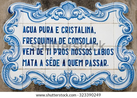 OVAR, PORTUGAL - SEPTEMBER 3, 2015: Panel of traditional Portuguese tiles hand-painted blue and white, with written quoted verses from a poem about water. - stock photo