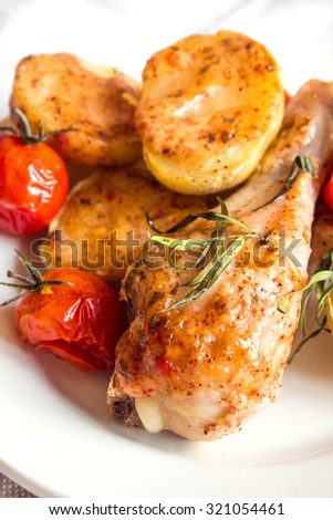 Oven baked chicken leg with vegetables (potatoes, tomatoes) spices and herbs on white plate