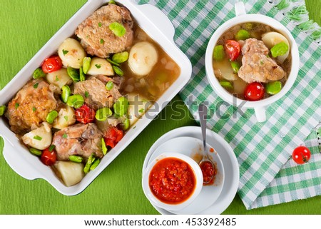 oven baked chicken things, new potatoes, tomatoes and butter lima bean in graten dish and in soup bowl on table mat, view from above - stock photo