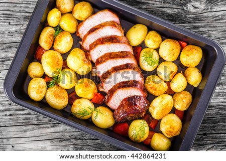 Oven Baked new potatoes with sea salt, red bell pepper and pork tenderloin cutting into pieces in a baking dish, on a wooden table, close-up, view from above - stock photo