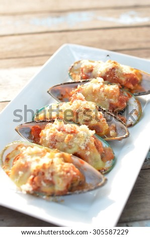 oven baked New Zealand mussels with cheese - stock photo