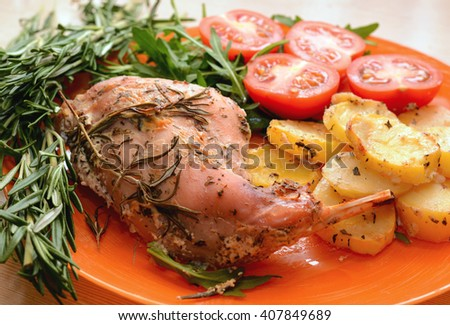 Oven Baked rabbit legs with potatoes and rosemary - stock photo