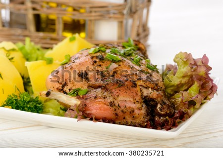 Oven baked rabbit with potatoes on white plate on wooden table. - stock photo