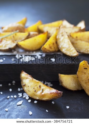 oven baked spicy potato slices on wooden desk served on paper with sea salt and rosemary. selective focus