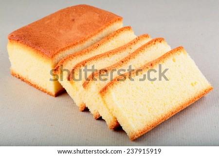 Oven fresh sliced sponge cake..Shallow depth of field photograph. - stock photo