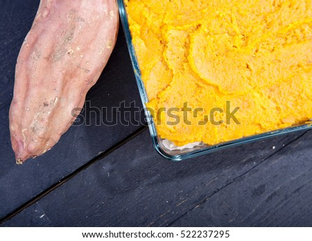 Oven meal with sauerkraut and sweet potato on wooden background