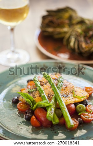 oven-roasted Arctic char with asparagus, tomatoes and olives with grilled artichokes appetizer and a glass of chardonnay - stock photo
