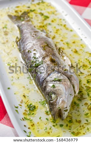 Oven roasted sea bass in rich brine from white wine, olive oil and parsley - stock photo