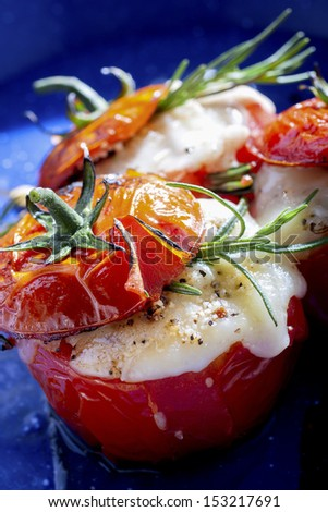 Oven roasted tomatoes stuffed with cheese in a blue pan - stock photo