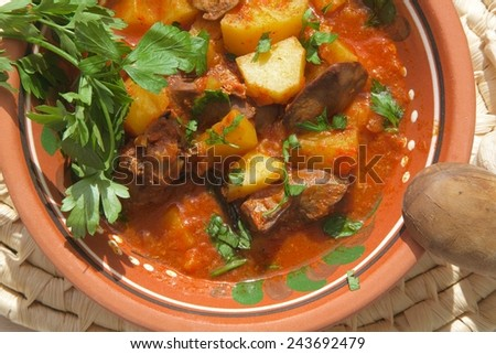 Oven stewed potatoes with chicken liver and tomatoes sauce in a traditional Moldovan clay plate. Served with fresh parsley. Wooden spoon, fresh garlic,and parsley leaves on a table. Top view.