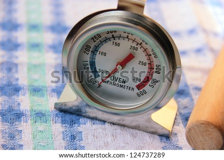 Oven thermometer and straight wooden rolling pin baking tools background.