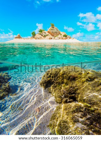 over and under water surface of a tropical atoll on a clear day - stock photo