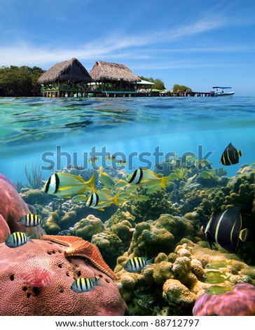 Over and underwater split view with a Caribbean restaurant over the sea and a coral reef with tropical fish, Crawl Cay, Caribbean, Bocas del Toro, Panama - stock photo