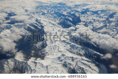 Over Austria en-route to Verona, Italy - May 2017: Aerial view of snow capped peaks in the alps partially covered by white clouds