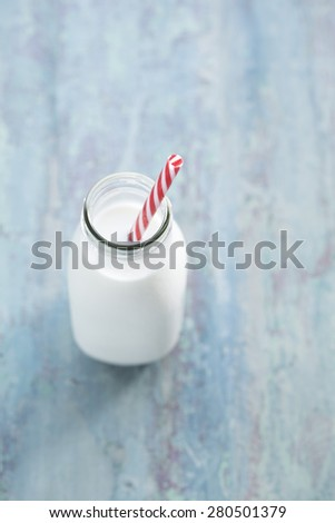 Over head biew of a Bottle of Milk with a red and white straw.  - stock photo