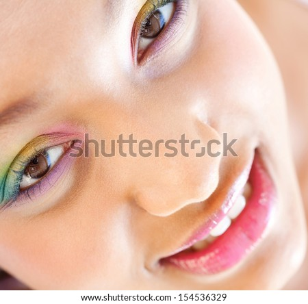 Over head close up beauty portrait of a young african american teenage girl wearing colorful fresh make up cosmetics and looking at the camera, smiling.