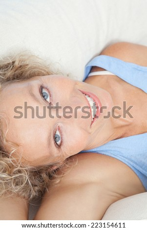 Over head close up beauty portrait of an attractive middle aged healthy woman relaxing on a white sofa at home, looking at the camera smiling. Interior home living and lifestyle.