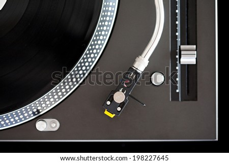 Over head close up detail view of a DJ turntable and vinyl ready to be used. Music equipment graphic view of a professional music deck, interior. - stock photo