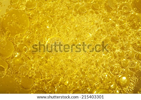 Over head close up full frame background detail view of golden shining yellow oil boiling and creating bubbles, indoors. Macro still life view of oil bubbles texture and detail. - stock photo