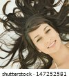 Over head close up portrait view of a beautiful teenager girl relaxing and laying down on a bed with her healthy and dark hair sprayed around her head, smiling at the camera. - stock photo