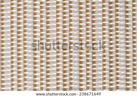 Over head close up view of a white and beige mat with interlinking stitches and vertical lines. Texture background with light colors and lines pattern. Abstract backdrop. - stock photo
