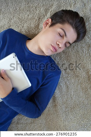 Over head portrait of young student man laying down on bed at home, asleep while hugging a digital tablet, interior. Technology at home. Studying and college lifestyle. Teenager fallen asleep indoors.