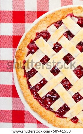 Over head shot of a cherry pie on red and white table cloth