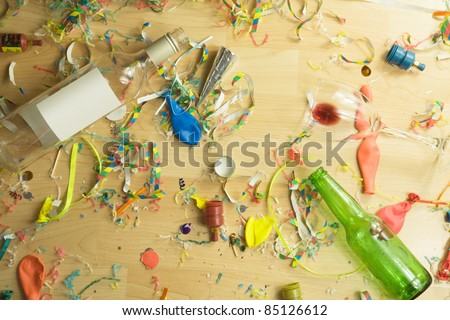 Over head shot of a wooden floor after a party celebration with empty bottles,wine glass and party decorations, - stock photo