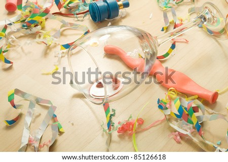 Over head shot of a wooden floor after a party celebration with empty wine glass and party decorations, - stock photo
