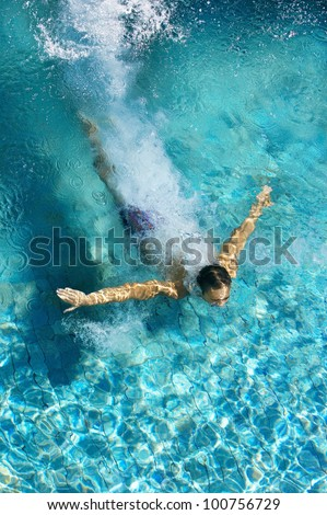 Over head view of a man diving into a swimming pool, forming an arrow shape and leaving a trace behind him.