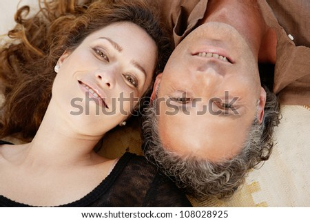 Over head view of a mature couple laying down on carpet at home, smiling. - stock photo
