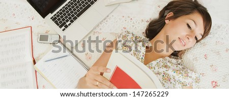 Over head view of a teenager student of languages doing her homework, laying on her bed in her bedroom with a laptop computer and cell phone, reading an open Spanish book. - stock photo