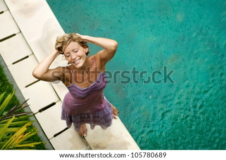 Over head view of a woman by a swimming pool under falling rain in the summer, smiling. - stock photo