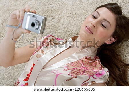 Over head view of a young attractive hispanic woman using a digital photo camera while laying down on a furry carpet at home, smiling. - stock photo