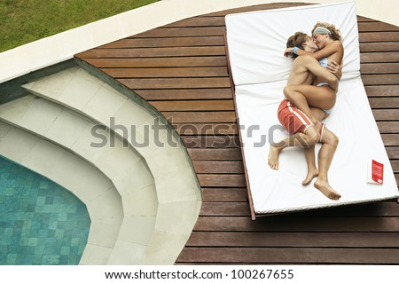 Over head view of a young couple playfully hugging and kissing on a sun lounger by the swimming pool.