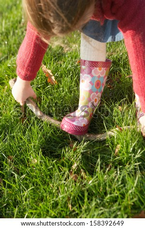 Over head view of a young little girl trying to break a tree branch while in a park with green grass during a sunny winter day outdoors. - stock photo